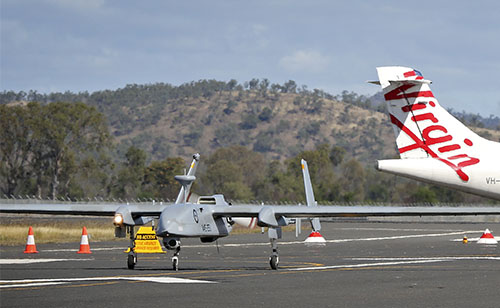 A Heron remotely piloted aircraft arrives at Rockhampton Airport in Queensland in front of a Virgin Australia civilian aircraft.