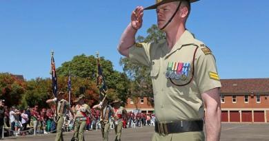 Corporal Donovan Murphy salutes as the colours of 7th Battalion, Royal Australian Regiment