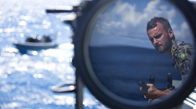 Sub Lieutenant Jackson Miller observes boat evolutions onboard HMAS Wollongong as she saisl across the Arafura Sea. Photo by Able Seaman Kayla Hayes.