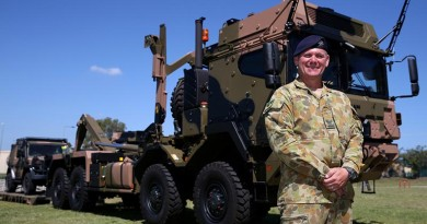 Corporal Grant Solomon, of the Land 121 Driver Training Team, shows off a new Rheinmetall MAN truck following the vehicle's acceptance under LAND 121 Phase 3B at Gallipoli Barracks. Photo by Corporal Max Bree.