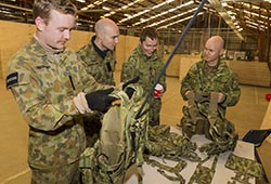 Australian Army officer Major Shane 'Buzz' Sarlin (right) from Diggerworks shows the new 'Tiered Body-Armour System (TBAS) Tier 0 Heavy' harness to soldiers at Exercise Hamel. Photo by Corporal Dan Pinhorn