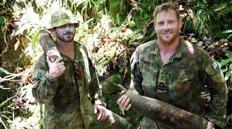 Navy Clearance Divers Petty Officer John Armfield and Lieutenant Robert Kelly carry WWII artillery shells in 'wild country' south of the village of Konga, south-east of Honiara, Solomon Islands.