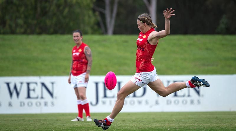 Australian Army soldier Private Kate Lutkins kicks for goal during a match at the ADF Australian Rules Championships in April 2016. Photo by Nunu Campos.