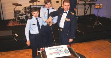 Group Captain Richard Trotman-Dickenson, with the most junior cadet and most senior cadet in uniform Cadet Adomas Neocleous and Cadet Under Officer Lachlan Renfrey, both from 619 ('City of Onkaparinga') Squadron at Seaford, cut the anniversary cake.