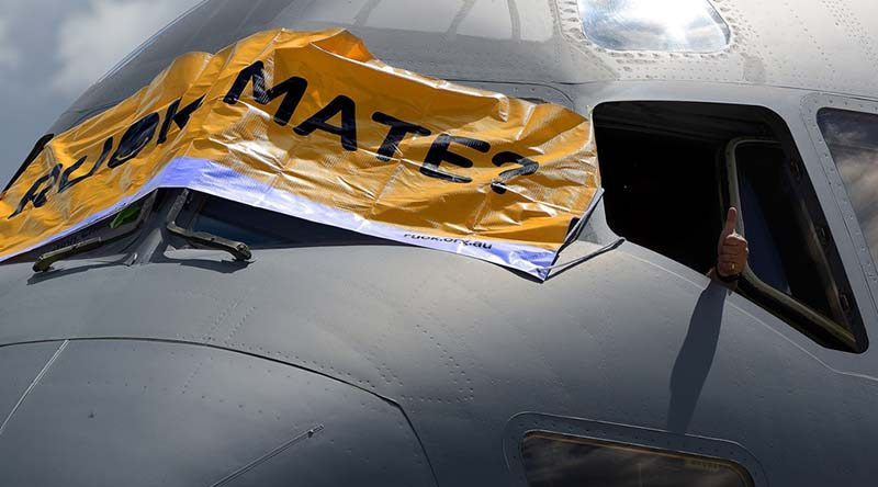 A thumbs up is given as a banner is placed across the front of an Air Force C-17A Globemaster aircraft to show support to mental health awareness on R U OK? Day at RAAF Base Amberley. Photo by Peter Longland.