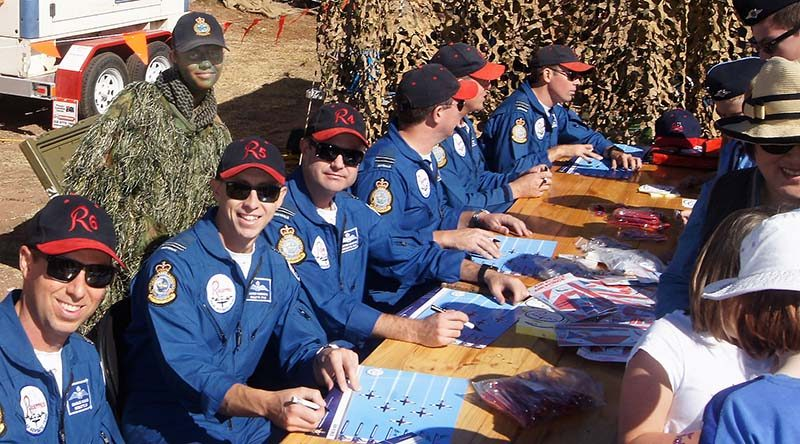 "Roulettes pilots autograph posters and give souvenirs to the public attending the 2017 Barossa Air Show, without noticing the photo-bomb by the Air Force Cadets' ""Ghillie Girl"". Photo by Pilot Officer (AAFC) Paul Rosenzweig."