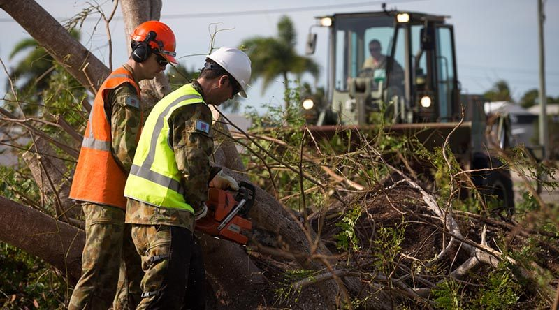 Corporal Brendan Bayly and a colleague from 3rd Combat Engineer Regiment, cuts up a fallen tree in Bowen, Queensland, in the wake of Tropical Cyclone Debbie. Photo by corporal David Said.