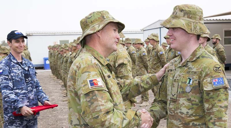 Wing Commander Philip Sexton congratulates his son Leading Aircraftman Caleb Sexton on receiving the Australian Operational Service Medal-Greater Middle East during the Theatre Communications Group (TCG) 3 medal parade in the Middle East on 20 February 2017. Photo by Corporal Bill Solomou.