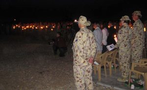 Sergeant Peter Rewko took this photo at the ANZAC Day Dawn Service at Talil, Iraq, in 2008 and sent it to CONTACT for publishing – not realising that CONTACT Editor Brian Hartigan is the civilian kneeling in centre of the picture.