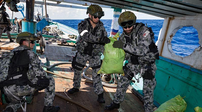 Members of HMAS Arunta's boarding party seize and account for illegal narcotics found during the search of a dhow while on patrol in the Middle East. Photo by Able Seaman Steven Thomson.