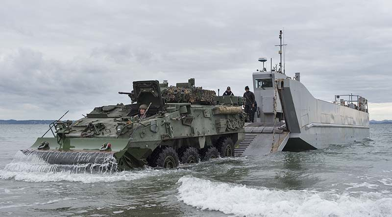 Army Corporal Robert Hosking drives a light armoured vehicle from a Navy landing craft. NZDF photo.