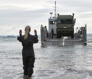 Greer Hutton of the anphibious beech team signals the driver of a MHOV to come forward off a landing craft. NZDF photo.