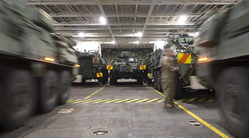 Two Light Armoured Vehicles (LAVs) are simultaneously driven into their parking spots onboard HMNZS Canterbury to be transported to Australia for Exercise Talisman Sabre.