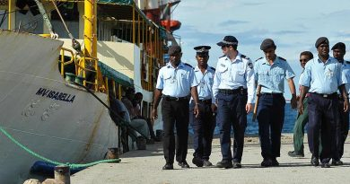 Australian Federal Police and Royal Solomon Islands Police Force patrol the dock at Honiara. AFP photo by Brian Hartigan.