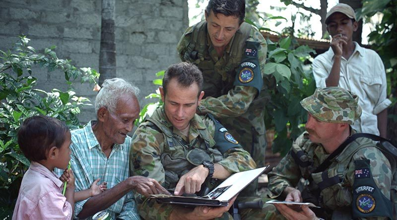 Then 75-year-old Rufino Correia, who worked with 2/2 Commando Squadron during WWII, reminisces with Australian soldiers in Dili, in 1999. Photo by Warrant Officer Class 2 Wayne Ryan.