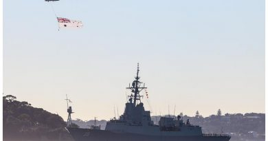 A Royal Australian Navy S-70B-2 Seahawk Helicopter flies the Australian White Ensign over NUSHIP Hobart as she sails past the HMAS Sydney I memorial for the first time. Photo by Petty Officer Kelvin Hockey.