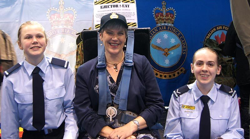 Principal of Urrbrae Agricultural High School Joslyn Fox strapped in to an ejector seat, attended by Cadet Jade Curwood (left) and Leading Cadet Ainsley Carter. Image by Flying Officer (AAFC) Paul Rosenzweig.