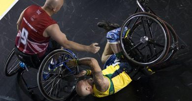 Former soldier Jeff Wright is assisted after a fall in a wheelchair basketball pool match against Denmark. Photo by Corporal Mark Doran.