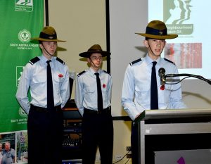 Cadet Ethan O'Connor gives an address during a Remembrance Day event, supported by Cadets Joshua Duncan and Darcy Needle.