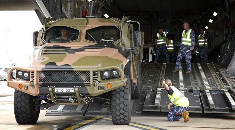 RAAF Base Amberley Air Movements personnel guide Australian Army WO2 James Moss as he reverses a Hawkei into a C-17A Globemaster. Photo by Corporal Ben Dempster.