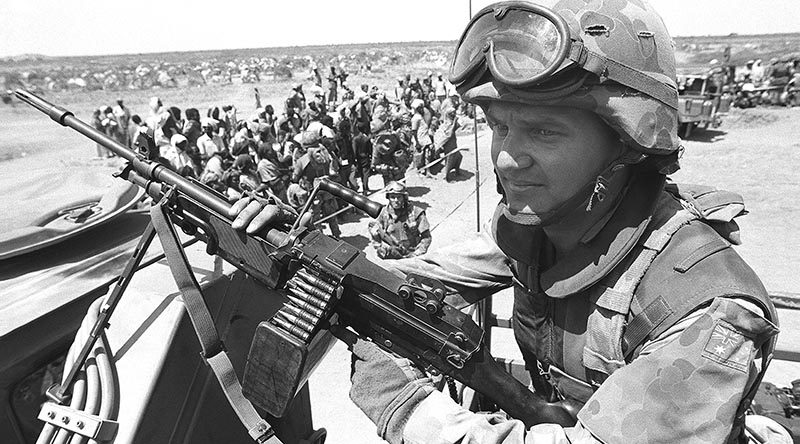Private AJ Shinner, 1RAR, stands guard over a food-distribution point near Baidoa. Photo by Corporal Gary Ramage – 21 Jan 1993.