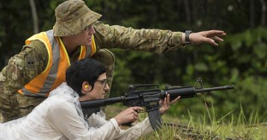 Australian Army officer Lieutenant Patrick Ingram supervises his civilian employer, Anita Gordon, as she prepares to fire an M4 carbine during Exercise Boss Lift in Malaysia. Photo by Sergeant Janine Fabre.
