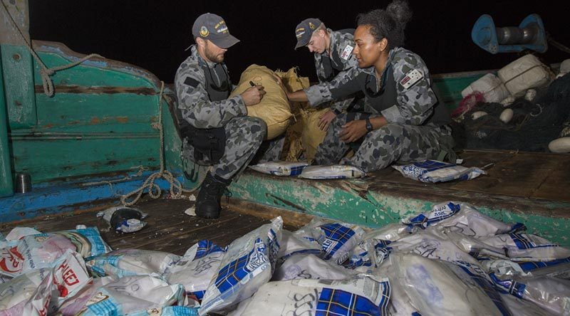 Royal Australian Navy sailors Leading Seaman Adam Cook, Able Seaman Dylan Canderle and Able Seaman Lydia Ratu Kavoa label and bag parcels of seized narcotics on a vessel in the Middle East. Photo by Leading Seaman Tom Gibson.