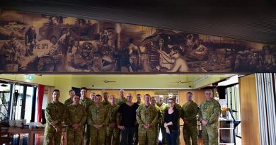 Artists Rob Douma and Kelly Bianchi pose beneath their mural with Chauvel Sergeants' Mess PMC WO1 Brent Doyle and other members of the Mess Committee.