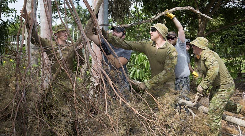 Royal Australian Navy members from HMAS Coonawarra help soldiers from 5RAR clean up debris after Tropical Cyclone Marcus. Photo by Leading Seaman James Whittle.