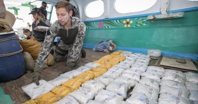 A sailor from Royal Australian Navy ship HMAS Warramunga prepares to remove packages of heroin from a dhow during a boarding operation. Photo by Leading Seaman Tom Gibson.