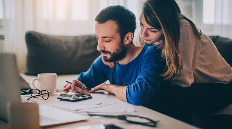 Couple sitting in their living room checking their finances. File photo supplied by Easifleet.