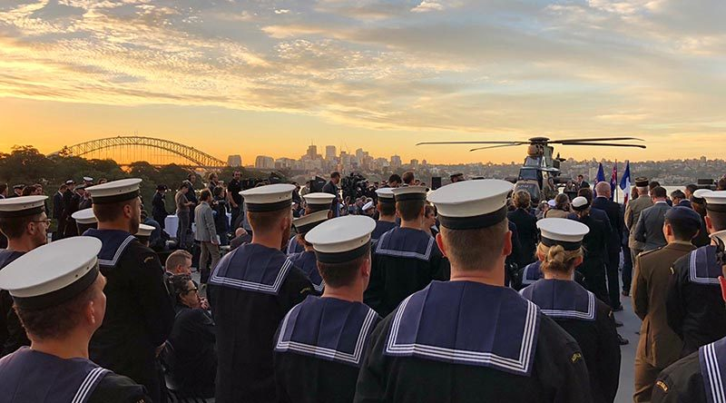 Royal Australian Navy personnel and guests listen to French President Macron onboard HMAS Canberra. Photo by Lieutenant Andrew Ragless.