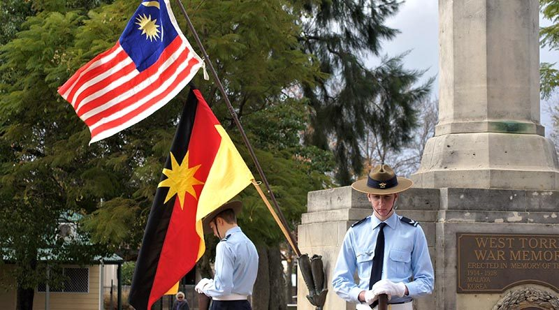 Australian Air Force Cadets CCPL Levi Schubert and CCPL Simon Russell from 604 Squadron Rest on Arms Reversed under the flags of Malaysia and Sarawak. Photo by Flying Officer (AAFC) Paul Rosenzweig
