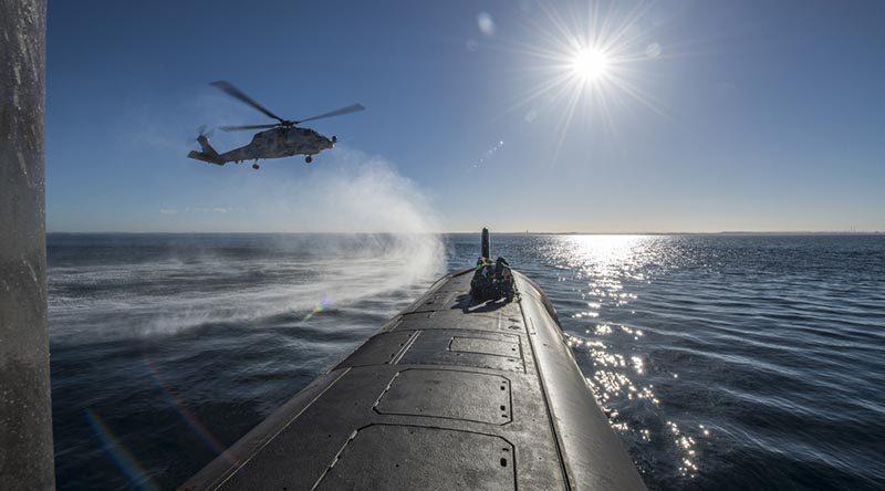 HMAS Ballarat's MH-60R Seahawk conducts a forward passenger transfer with HMAS Rankin in Western Australia, before the submarine departs for RIMPAC18. Photo by Able Seaman Grahame Kelaher.