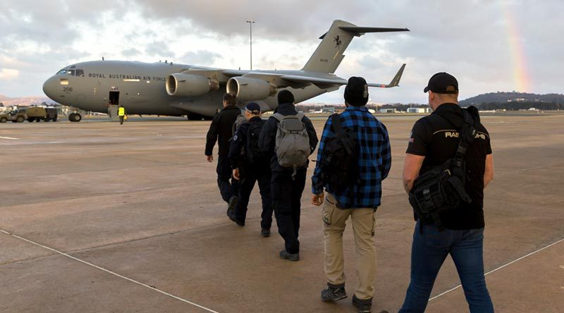 Australian Federal Police Specialist Response Group members and an official from Department of Foreign Affairs and Trade board a Royal Australian Air Force C-17A Globemaster at Canberra Airport to assist in the international search and rescue effort for children missing in a cave complex in Thailand. Photo by Sergeant Ray Vance.