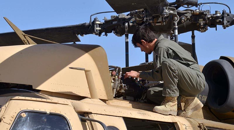 An Afghan Air Force member inspects a UH-60 Black Hawk at Kandahar Air Field, Afghanistan, as air crews prepare for their first Afghan-led operational mission on this aircraft type. US Air Force photo by 1st Lieutenant Erin Recanzone.