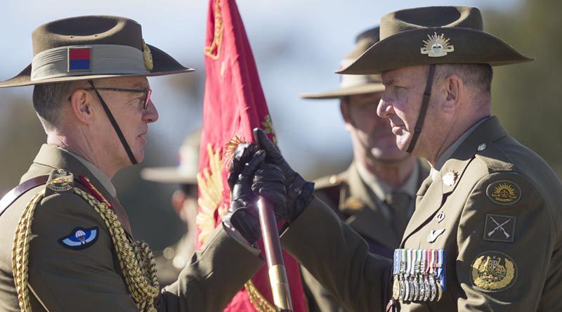 New Chief of Army Lieutenant General Rick Burr passes the Australian Army Banner to new Regimental Sergeant Major - Army, Warrant Officer Grant McFarlane. Photo by Corporal Tristan Kennedy.