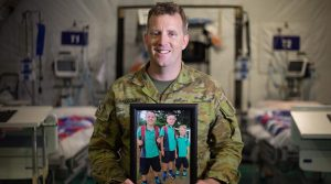 Australian Army Lieutenant Shane Balcombe displays a photo of his three boys, at Taji Military Complex, Iraq. Photo by Corporal david Said.