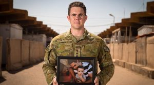 Australian Army Captain Evan Smith holds a photo of his son at Taji Military Complex, Iraq. Photo by Corporal David Said.