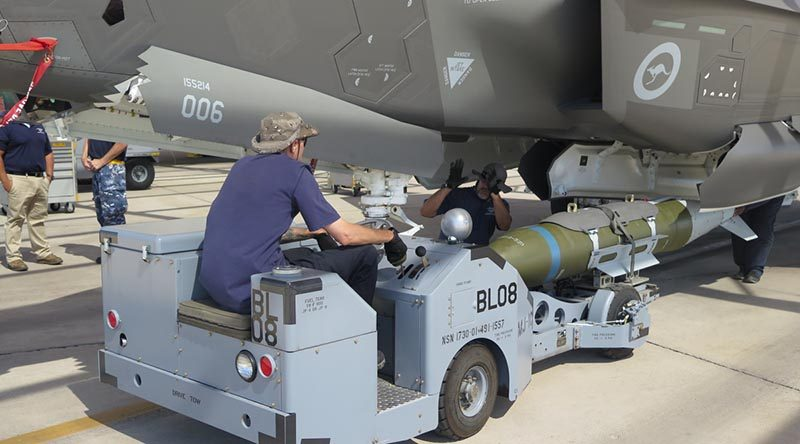 Lockheed Martin personnel load one of the first inert GBU-31 guided bombs into an Australian F-35A Joint Strike Fighter. Photo by Larone Thomas.