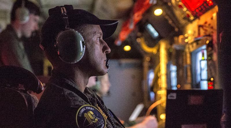 Royal Australian Air Force Warrant Officer David Bradshaw monitors a radar onboard an AP-3C Orion during a night exercise in the Philippines. Photo by Leading Seaman Jake Badior.
