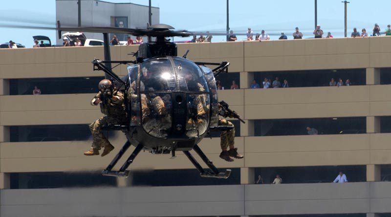 Special operations operators onboard an MH-6 Little Bird helicopter assault a simulated enemy position in an urban setting during a capabilities demo at the 2018 International Special Operations Forces week in Tampa, Florida. Photo by US Air Force Master Sergeant Barry Loo.