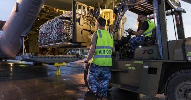 RAAF Corporal Adam Parrington guides Leading Aircraftman Madison Dukes, while loading a C-130J Hercules with humanitarian-aid supplies in Balikpapan as part of Operation Indonesia Assist 2018. Photo by Leading Seaman Jake Badior.