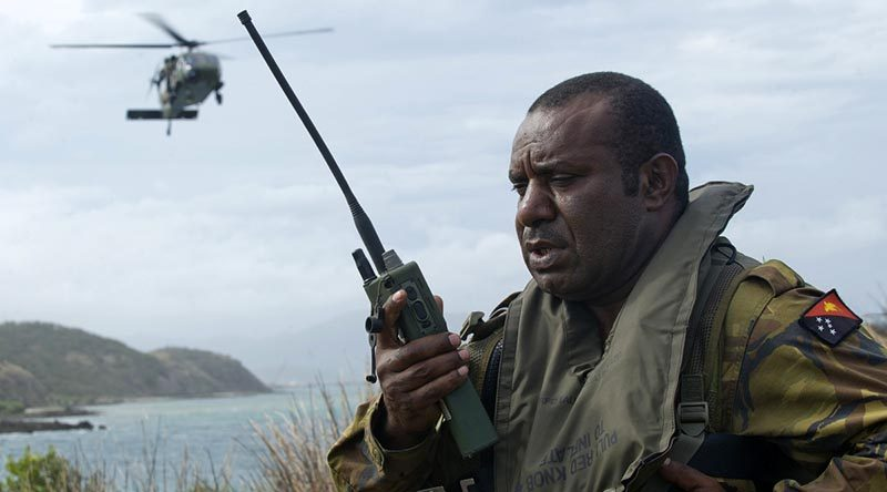 A Papua New Guinea Defence Force soldier conducts a landing-zone briefing and coordinates the extraction of military personnel by an Australian Army Black Hawk helicopter in Papua New Guinea during an exercise. Photo by Leading Seaman Justin Brown.
