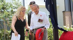 Gordon Jamieson lay a wreath at Carinity Cedarbrook at Mudgeeraba, Queensland, assisted by Wendy Kane and Rye Stott.
