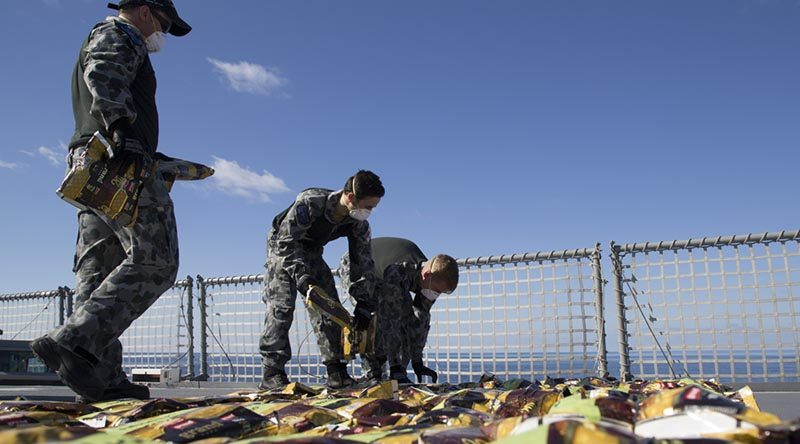 Members of HMAS Ballarat's boarding party lay out seized narcotics in preparation for disposal in the Middle East. Photo by Leading Seaman Bradley Darvill.