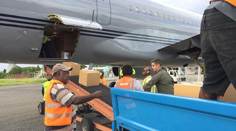 Flight Lieutenant Sam Hatrick, aircraft captain from the Royal New Zealand Air Force's No.40 Squadron, helps offload about two tonnes of voting equipment and operational supplies for The Fred Hollows Foundation New Zealand from an RNZAF Boeing 757 aircraft at Honiara. NZDF photo.