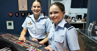 Cadet Sergeant Lucy Tassell and Cadet Charlotte Tassell with the World War 2 medals of their great-grandfather, Leading Aircraftman Owen Forrest, RAAF.