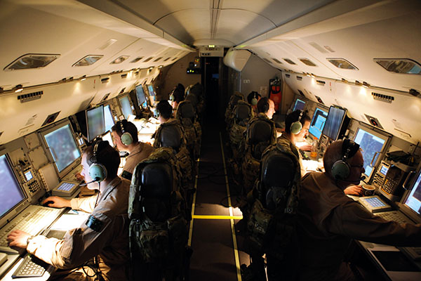 The crew of an E-7A Wedgetail at their consoles during a mission over Iraq.