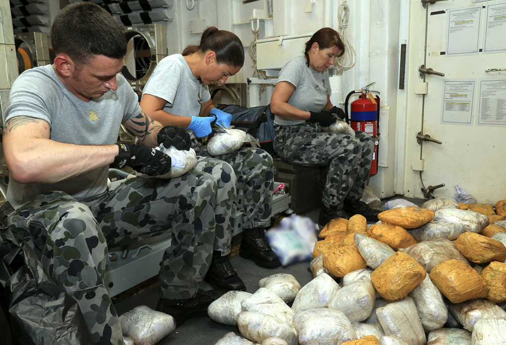 Seized drugs are unwrapped and sorted by HMAS Newcastle crew members.
